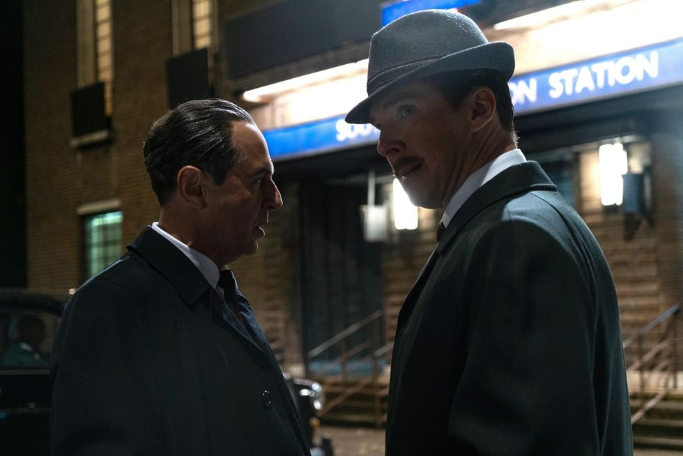 """Merab Ninidze (standing left) and Benedict Cumberbatch (standing to the right, looking to the left) in a movie still photo from """"The Courier."""" Both men are wearing dark suits. It's the early 1960's, and the men are standing outside on a dark street in front of a train station entrance."""