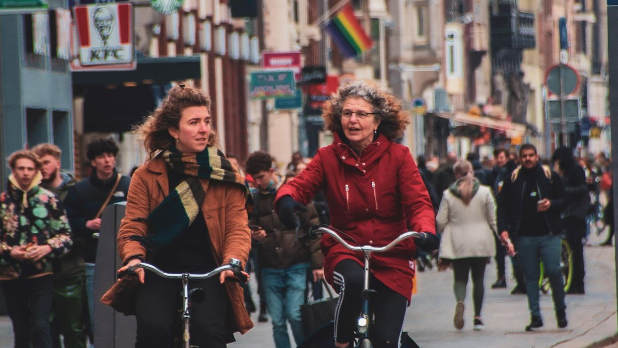 Two women on bicycles in the Netherlands on a crowded street.