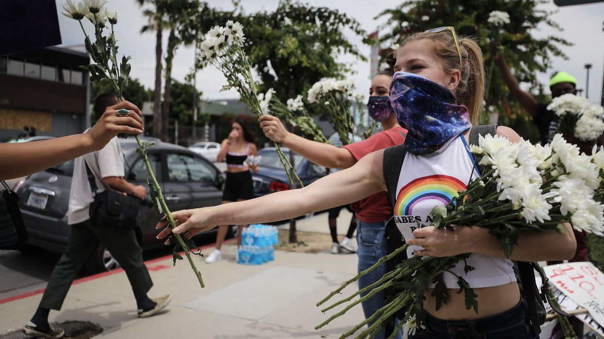 Supporters pass out flowers to protesters along Hollywood Boulevard during a peaceful demonstration over George Floyd's death on June 2, 2020 in Los Angeles, California.
