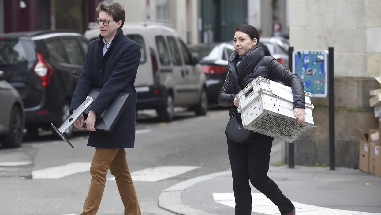 A man and a woman carry office supplies home to enable working from home due to the coronavirus restrictions.