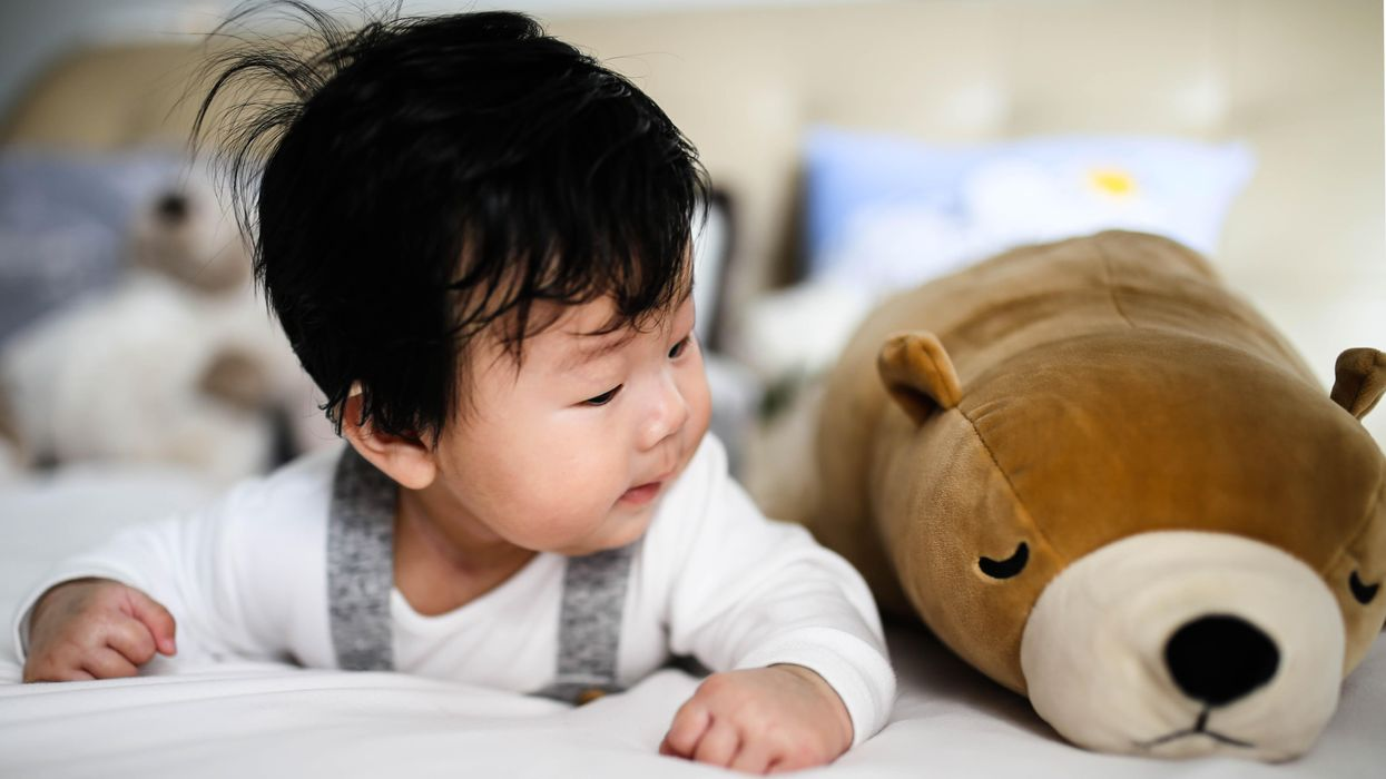 A baby lies on the bed looking at a toy bear.