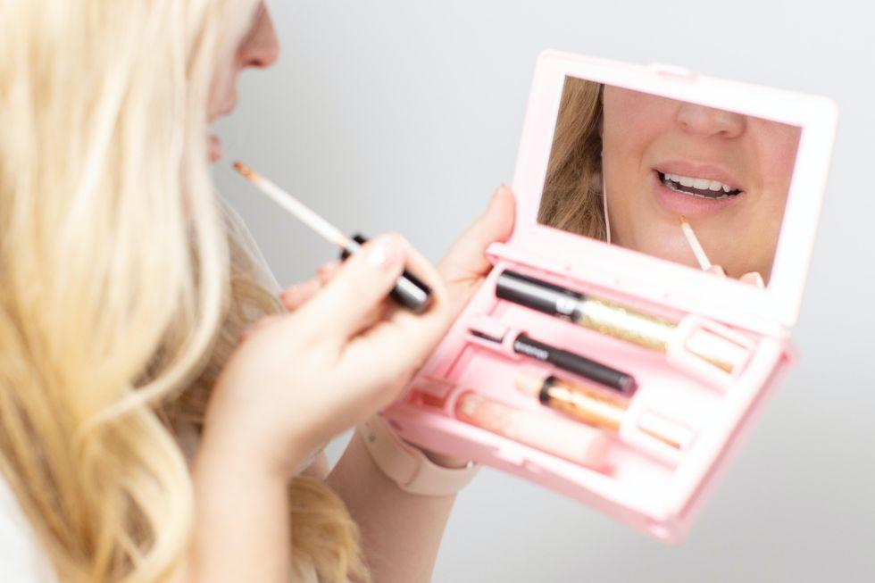 woman holding lip gloss set