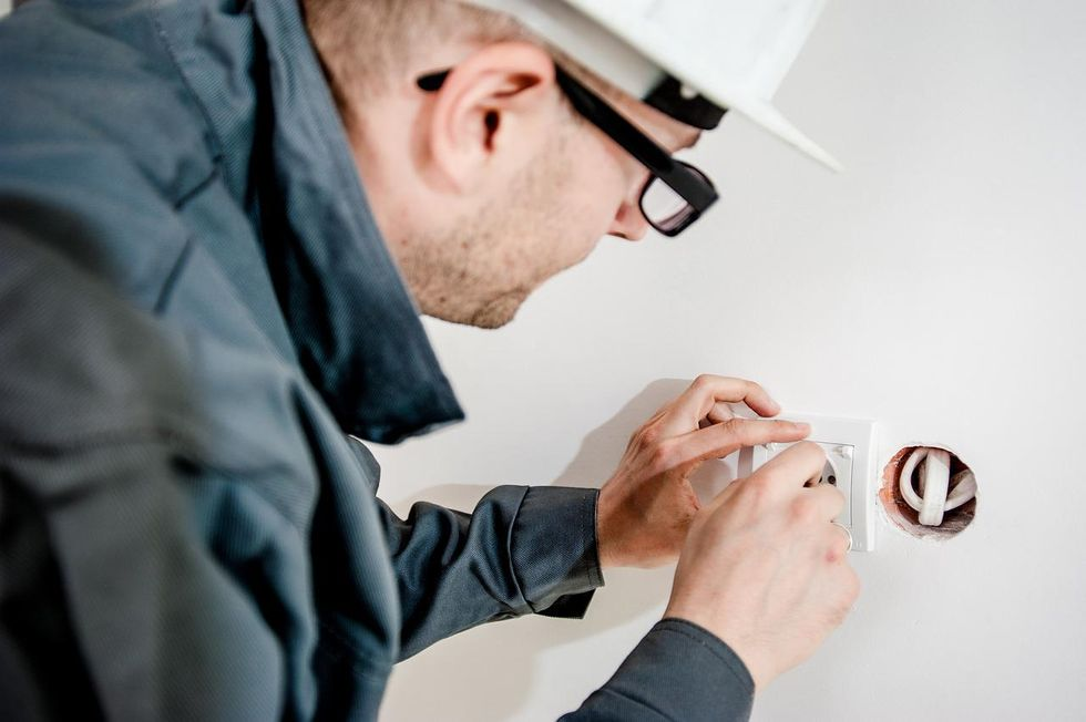Electrician Plugging In Socket