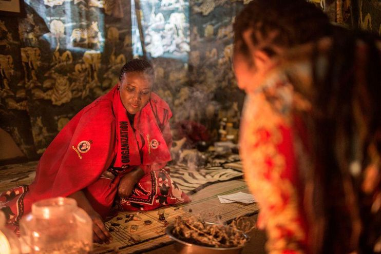 A traditional healer dressed in red and black traditional gear.
