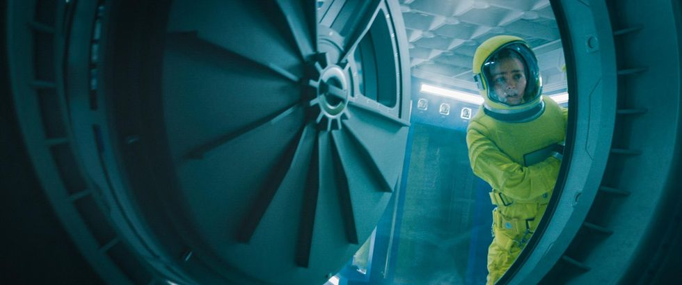 """Sela looks outside of an air duct on a spaceship in sci-fi thriller """"Voyagers."""" Actor Lily-Rose Depp is wearing a bright yellow hazmat suit while peeking outside the air duct that opens to space."""