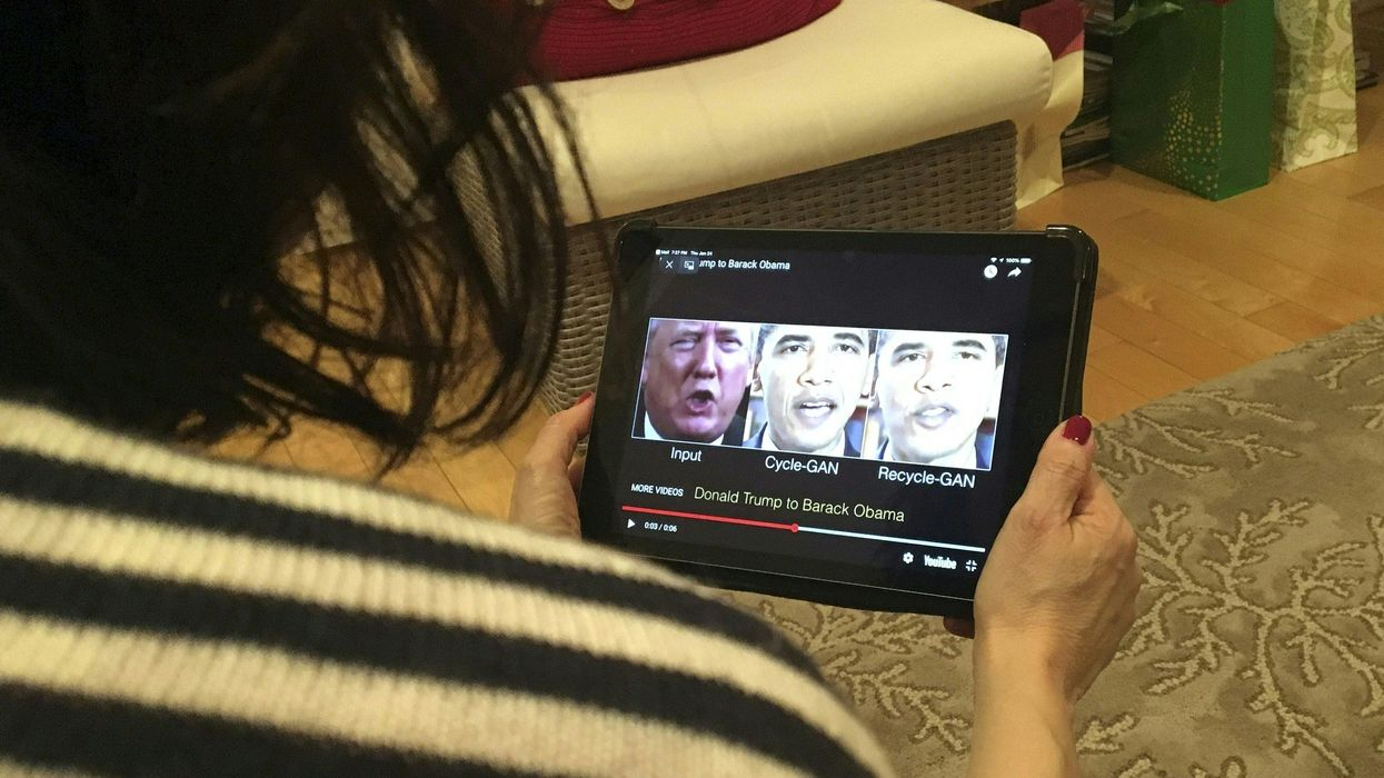 A woman looking at a tablet that shows a video of a deepfake.