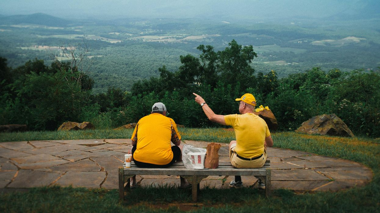 Two men wearing bright yellow shirts sitting on a bench and looking over a green valley.