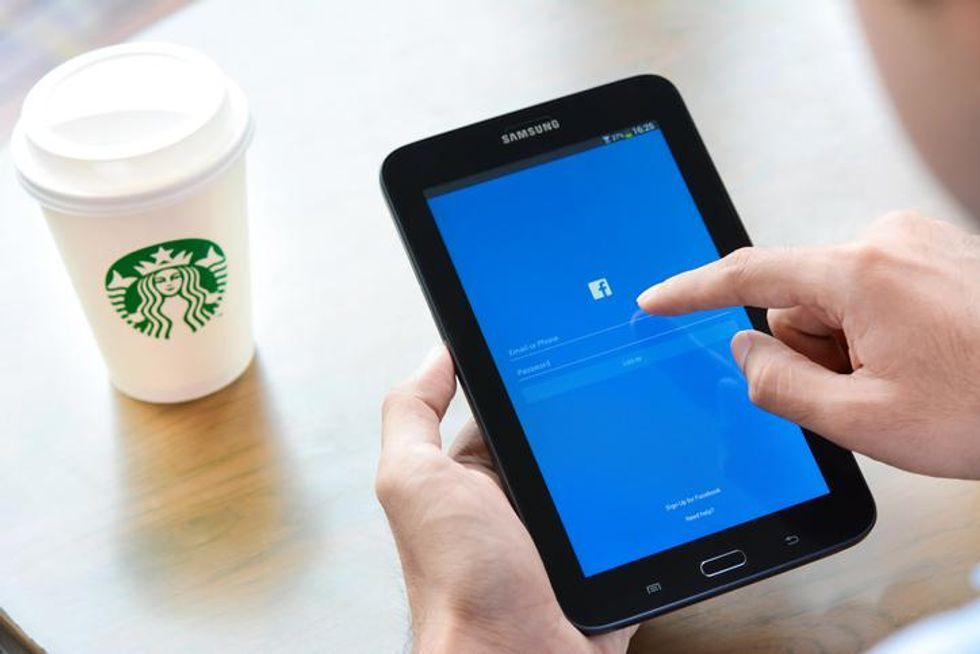 Person holding Samsung tablet while logging in to Facebook with cup of Starbucks coffee