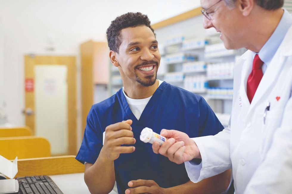 A pharmacy technicians chats with his boss.