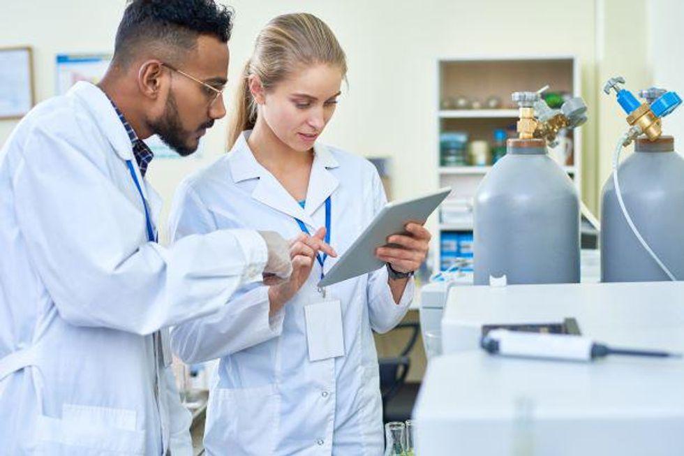 Pharmacy technicians consult over a prescription.