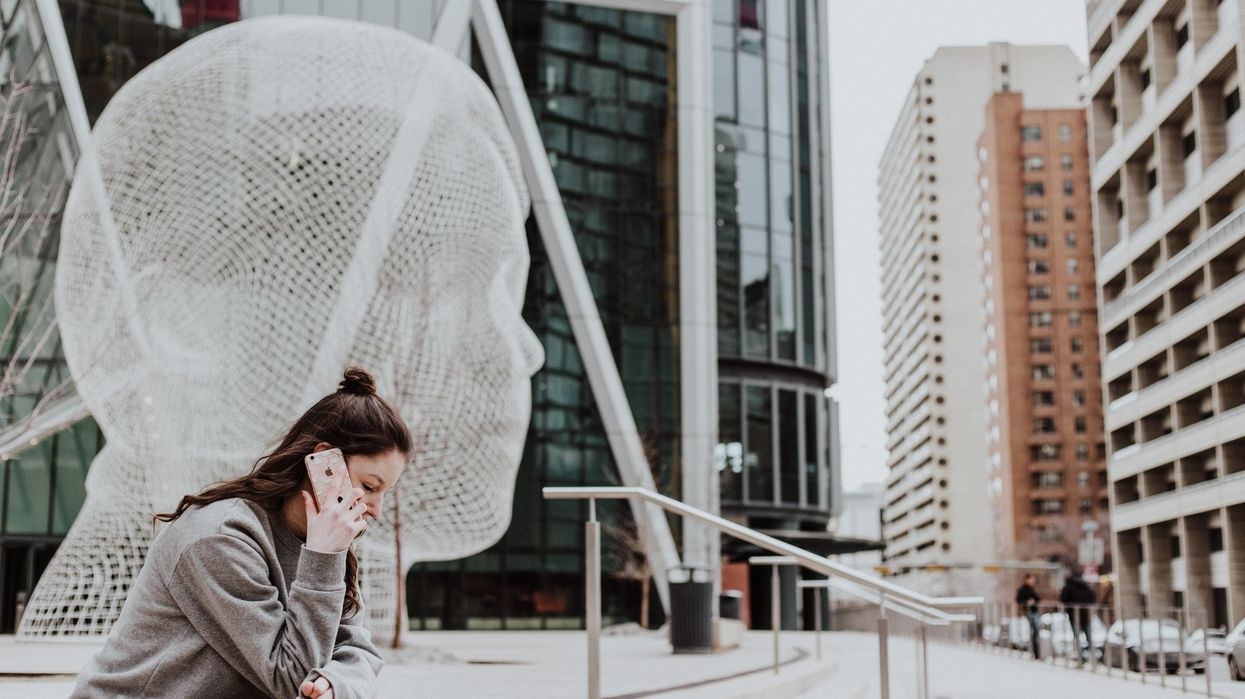 A woman talking on a cell phone outdoors next to a sculpture.