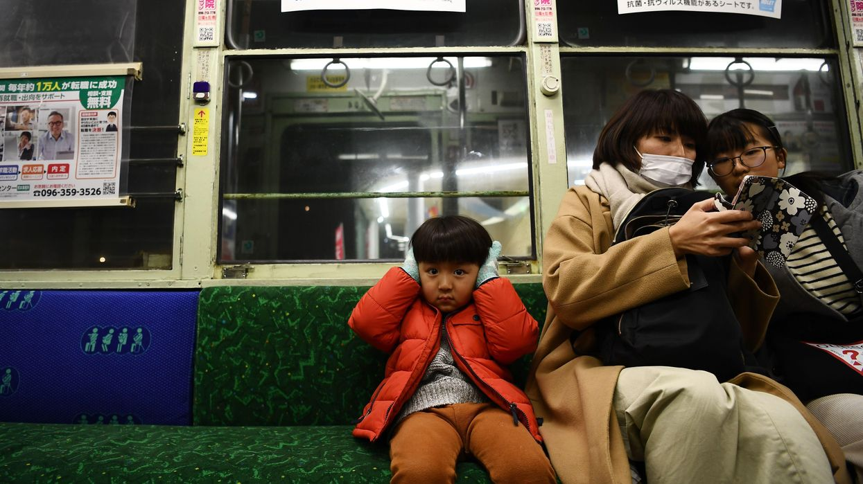 A child covers his ears against the noise on an underground train.