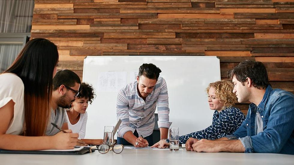 Man leads his team at work