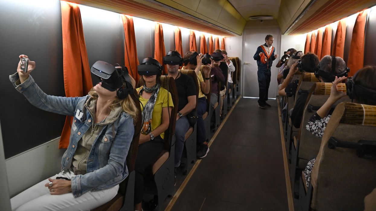 Journalists attend a press tour at Timeride, a company offering Virtual Reality tours through a still-divided Berlin, on August 22, 2019 in Berlin.