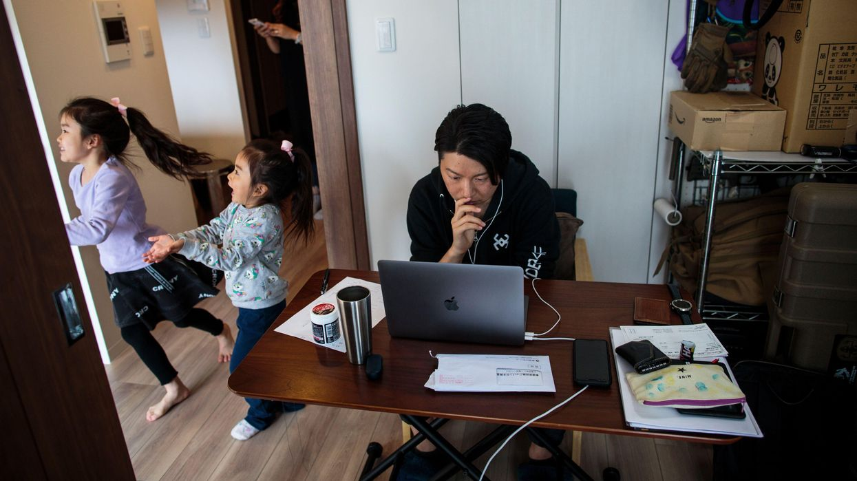 An employee in a startup company, working from home as a result of the COVID-19 novel coronavirus as his daughters play and his wife uses a mobile phone.