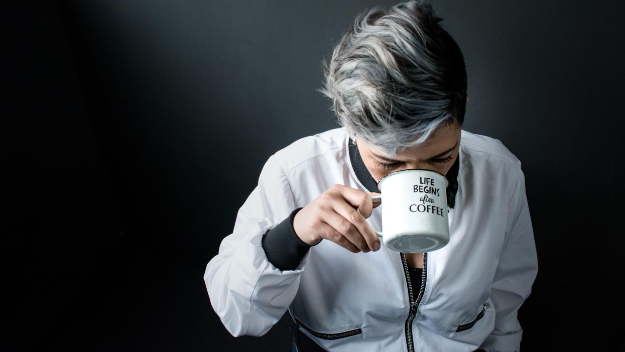 A woman in a white jacket sipping coffee in front of a black backdrop.