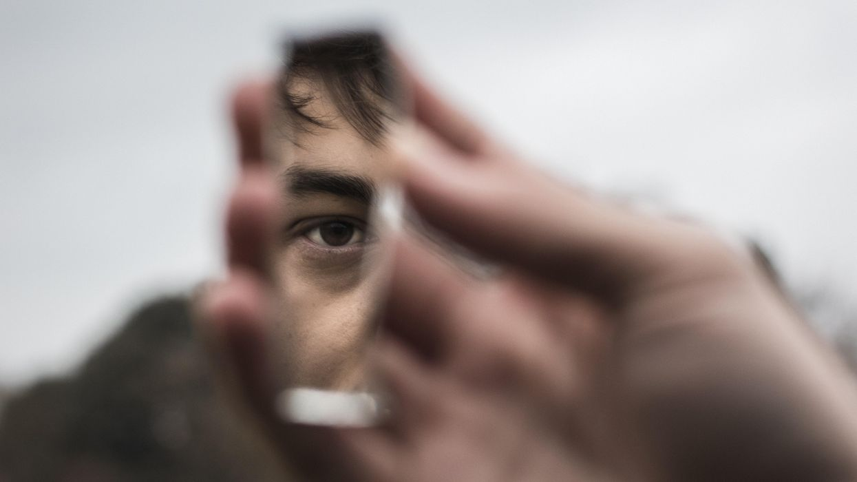 A man holds a fragment of a mirror, where his eye is visible.