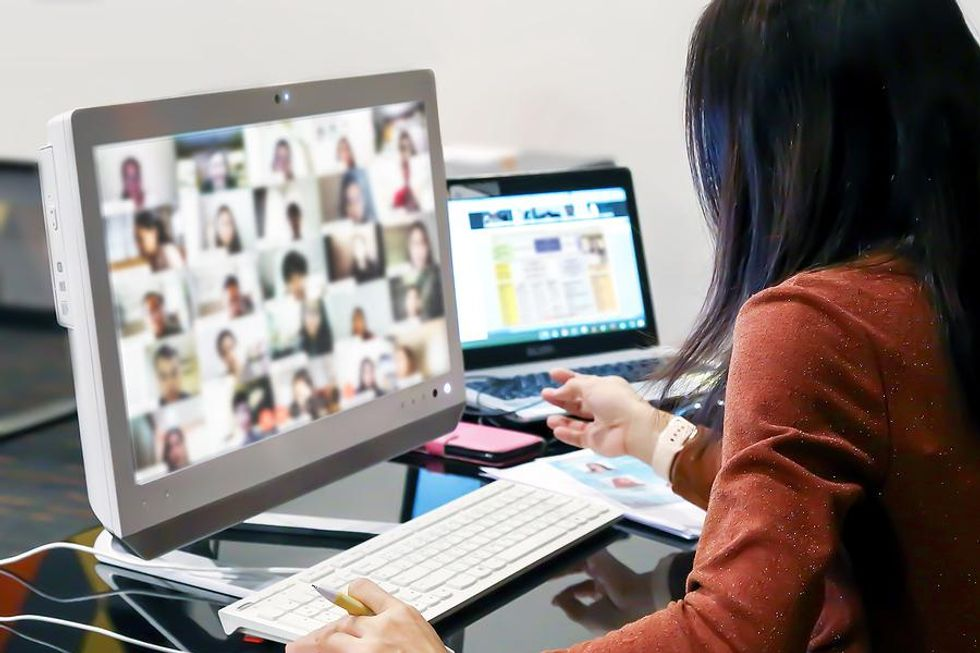 A group of coworkers take part in a weekly Zoom meeting.