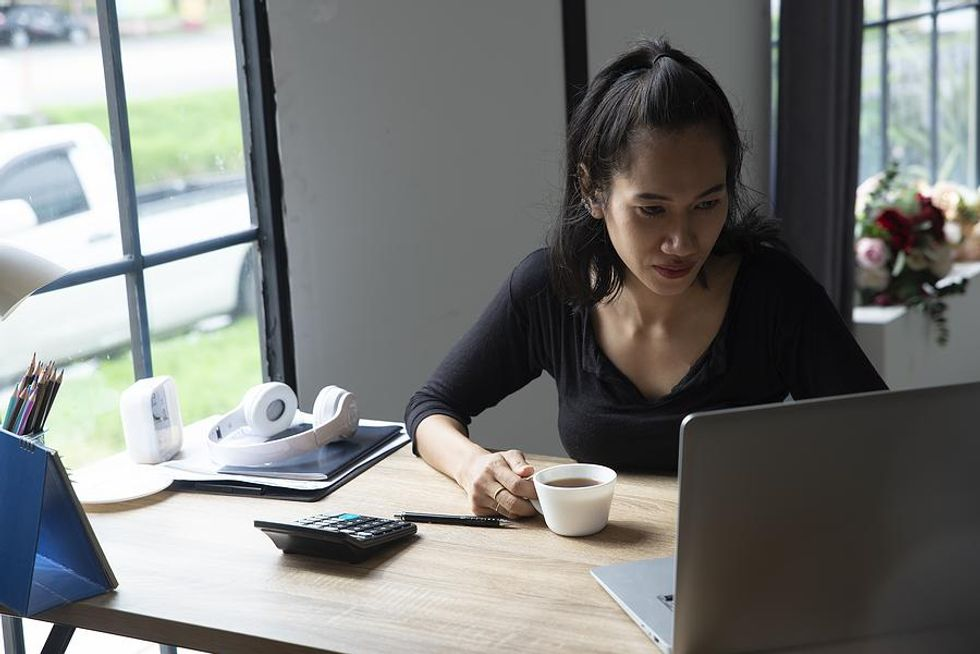 A businesswoman works with intense focus from her home office.