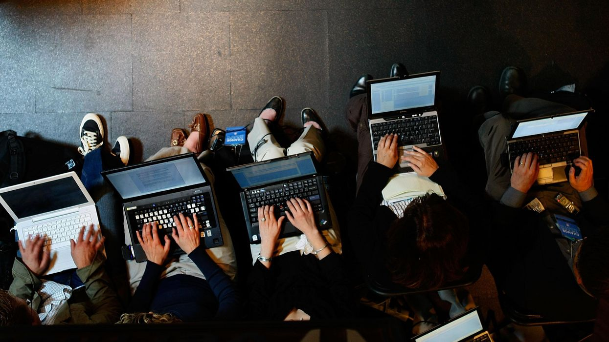 An overhead shot of five people working on laptops sitting next to each other.