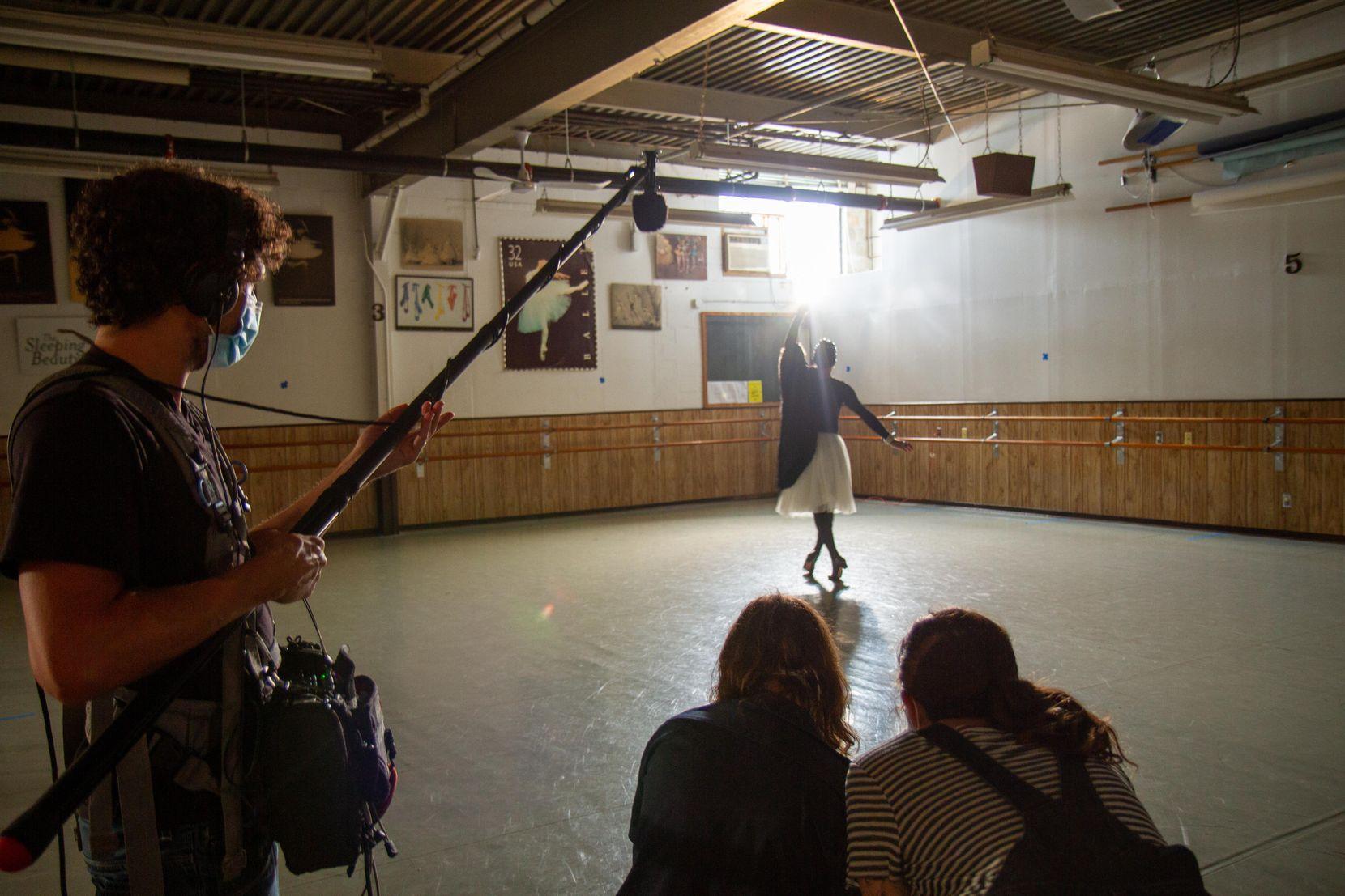 Madame Olga dances in a ballet studio, as a camera crew films her.