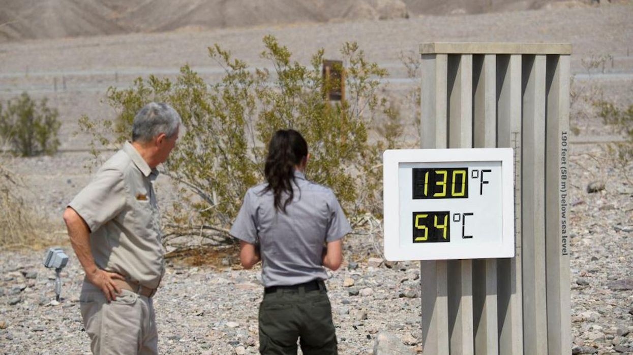 Park staff take pictures of a thermometer display showing temperatures of 130° Fahrenheit in Death Valley, California.