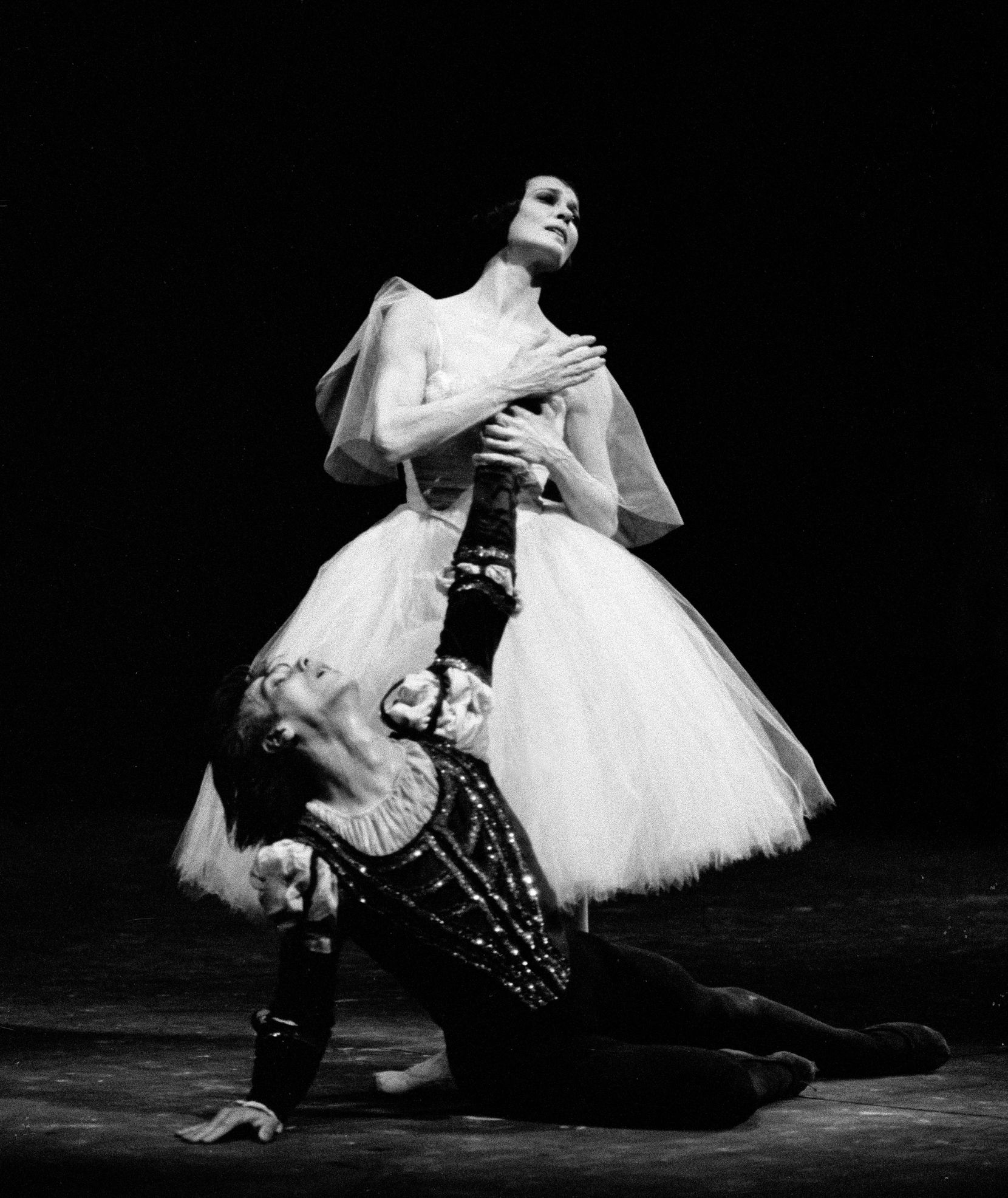 In this black and white photo, Carla Fracci stands above Gheorghe Iancu, who lies in a heap on the stage floor, during a performance of Giselle. She grabs his left hand and holds it to her heart while he looks up at her desperately. She wears a white Romantic tutu while he wears a dark mediaeval-style prince tunic and dark tights.