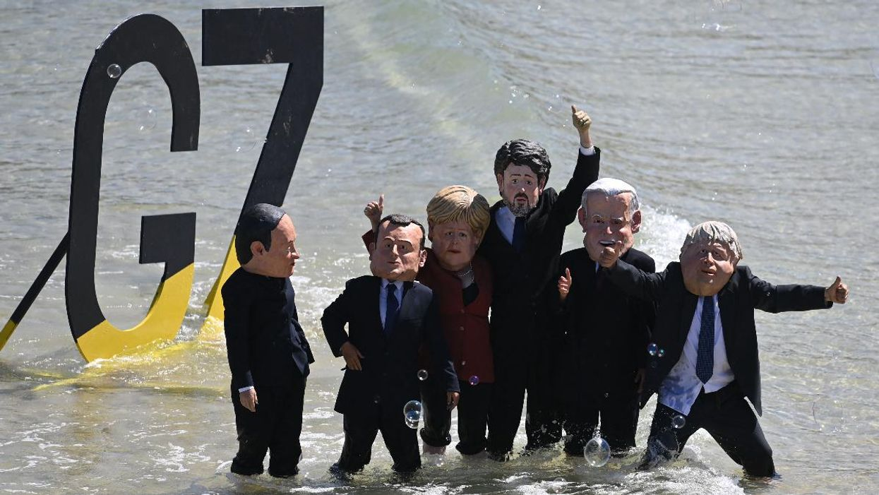 Environmental activists wearing masks of G7 leaders protest on the beach during the G7 summit.