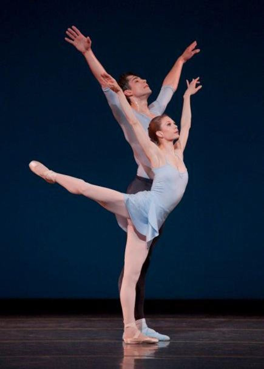 Gavin Larsen\u2014in a light blue leotard and skirt, pink tights and pointe shoes\u2014stands on her left leg with her right leg in a high arabesque and holds her arms up in a V-shape. Behind her, Artur Sultanov stands in sixth position with his arms in the same V-shape, and wears black tights, a blue T-shirt and blue socks and ballet slippers.