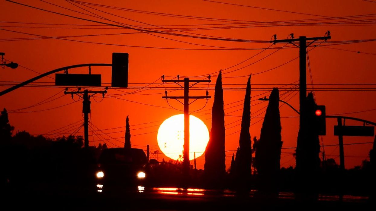 The sun sets behind power lines in Los Angeles, California before a heatwave.