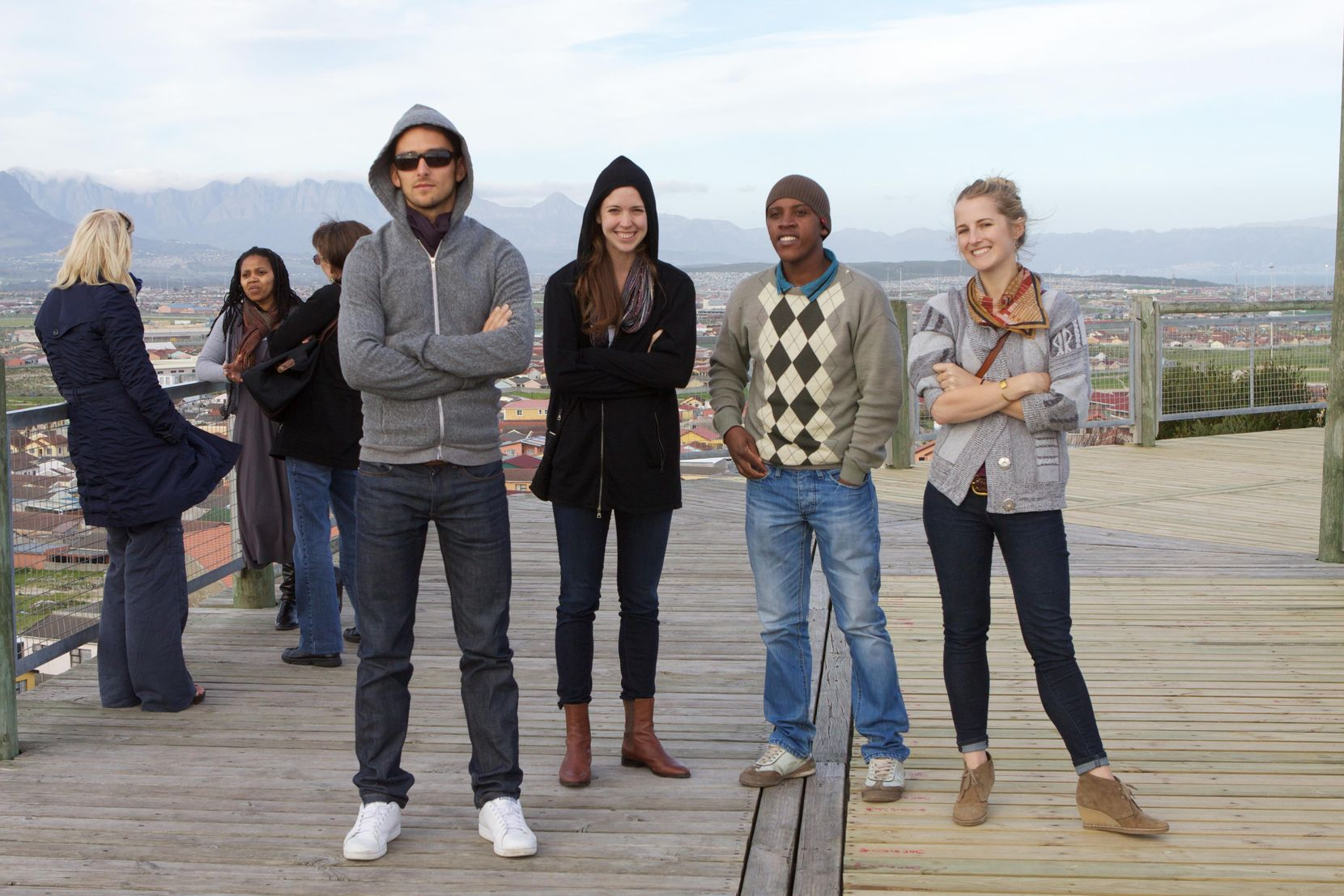 A group of two men and two women stand on a wooden deck overlooking a town and smile towards the camera. They wear jeans and assorted jackets, sweaters or sweatshirts.