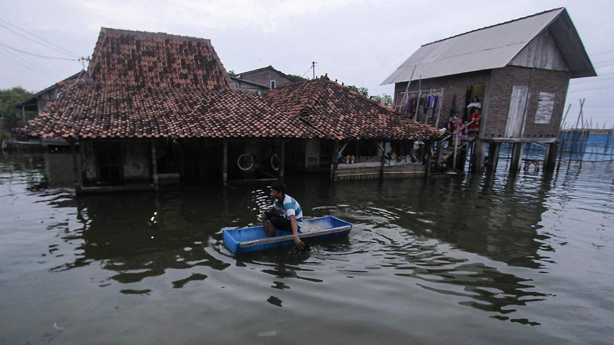 A man uses a handmade boat to reach his flooded home in Indonesia.