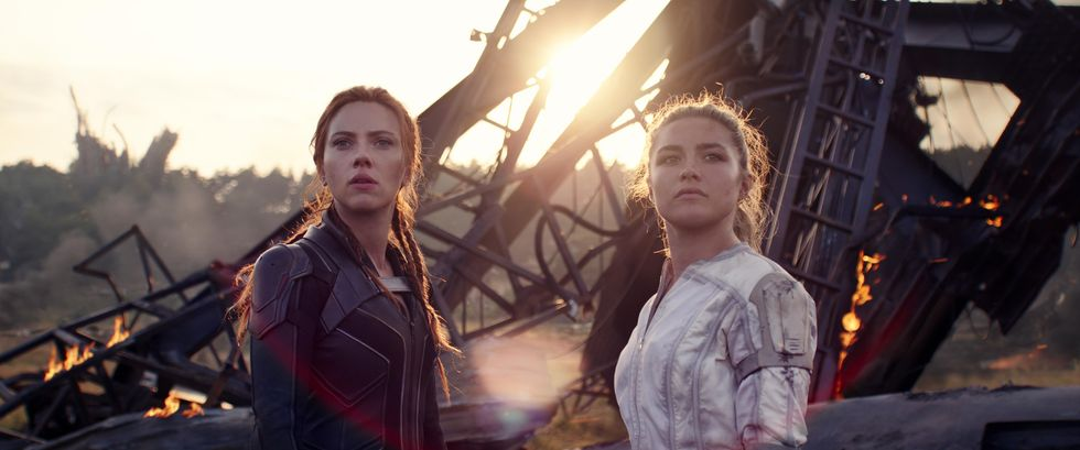 """Scarlett Johansson (left) as Black Widow and Florence Pugh (right) as Natasha's sister Yelena Belova look past the camera in a movie still from """"Black Widow."""" The sisters seem to have survived a calamity as there is lots of wreckage and metal bars in the background."""