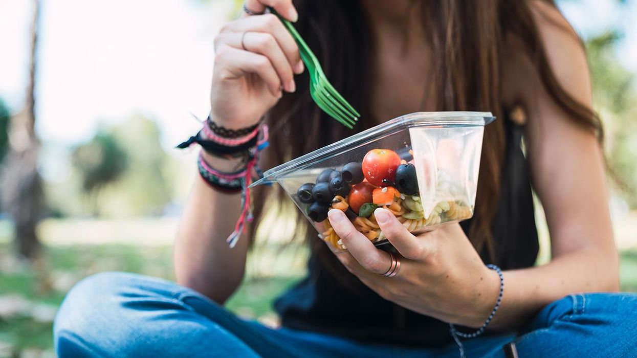 woman eating lunch at park from plastic container