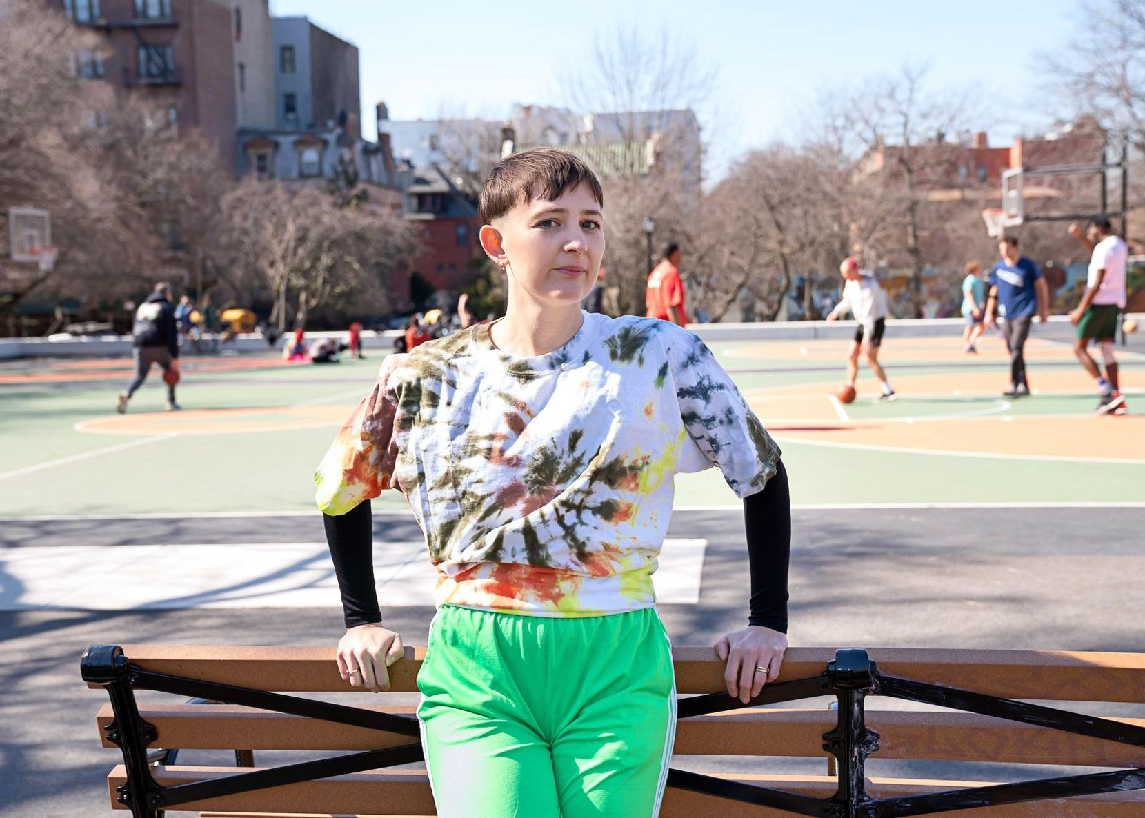 Katy Pyle leans on a park bench dressed in bright green sweatpants and a white tie-dye shirt