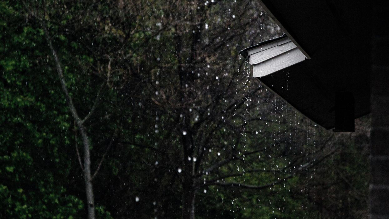 Rain falls off a roof of a cabin in the woods.