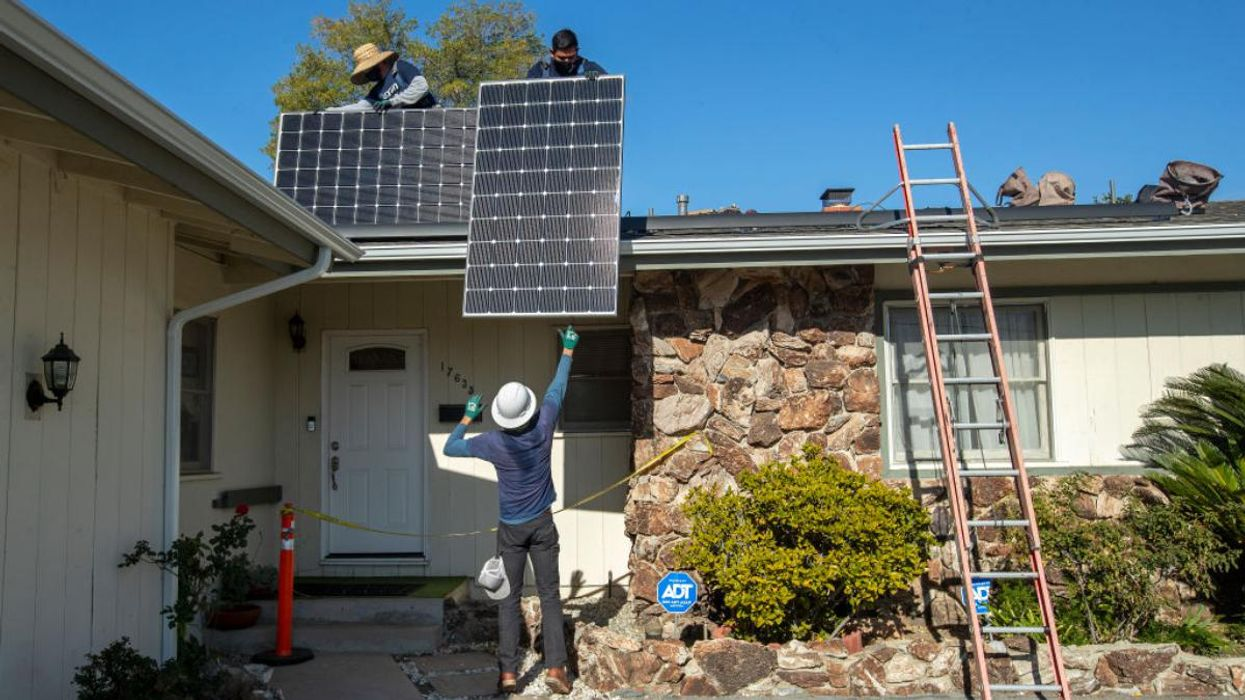 Solar workers install a rooftop system.