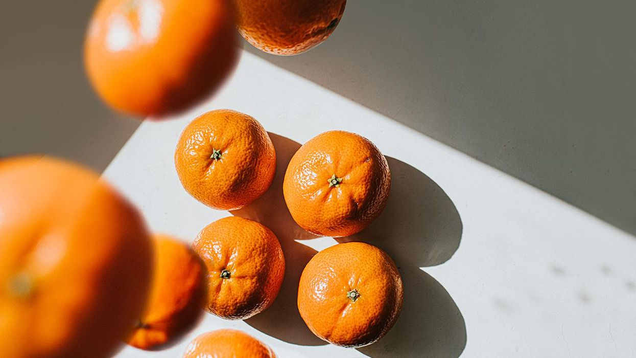 Mandarin oranges sit on a white surface while others fall from above