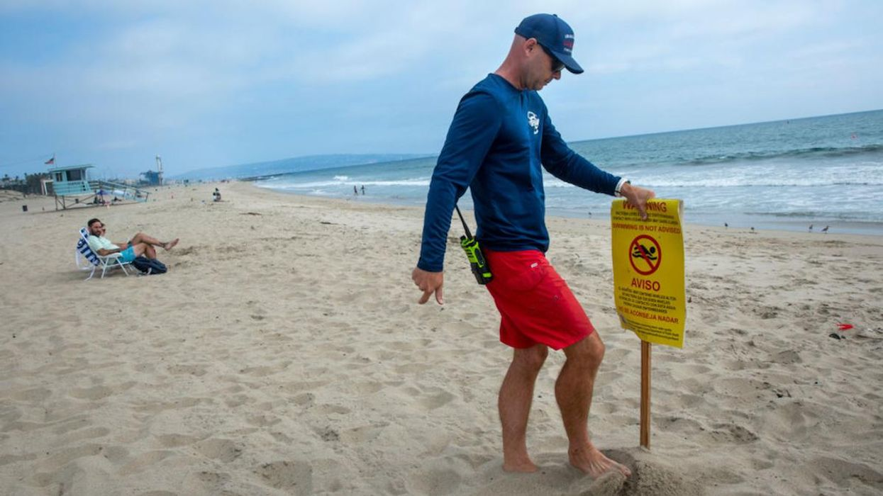 A lifeguard puts out a sign warning that swimming is not advised.