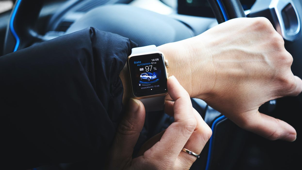 Close up of a woman's hands checking her Apple watch while driving.