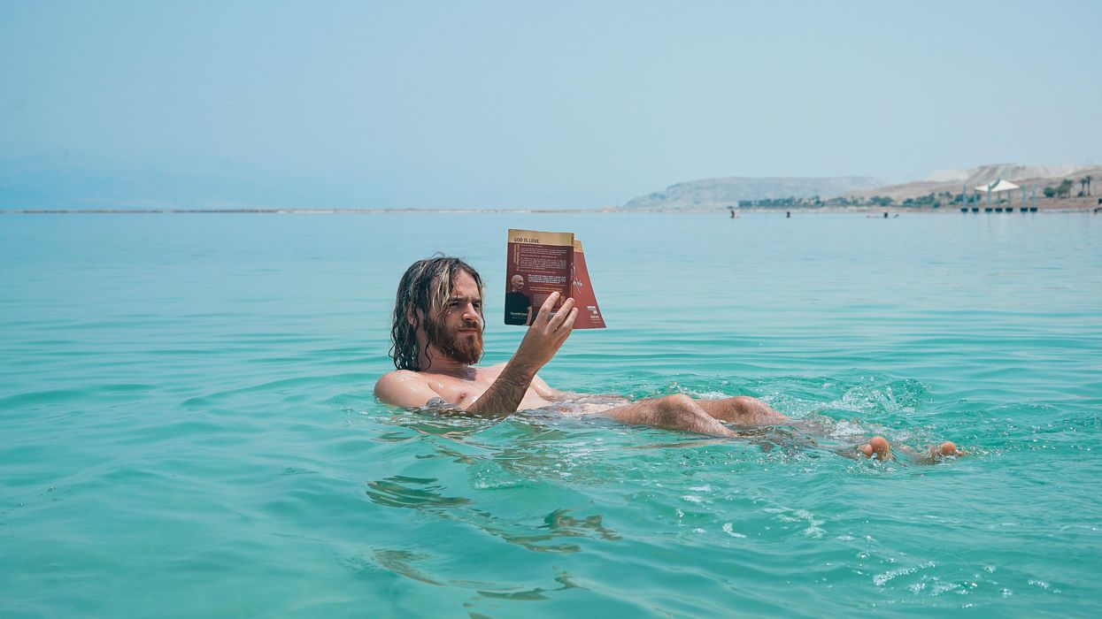 Man floating in the Dead Sea and reading a book.