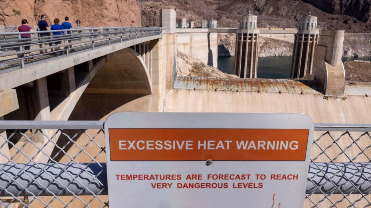 """A sign at Hoover Dam warns of """"very dangerous levels"""" of heat."""