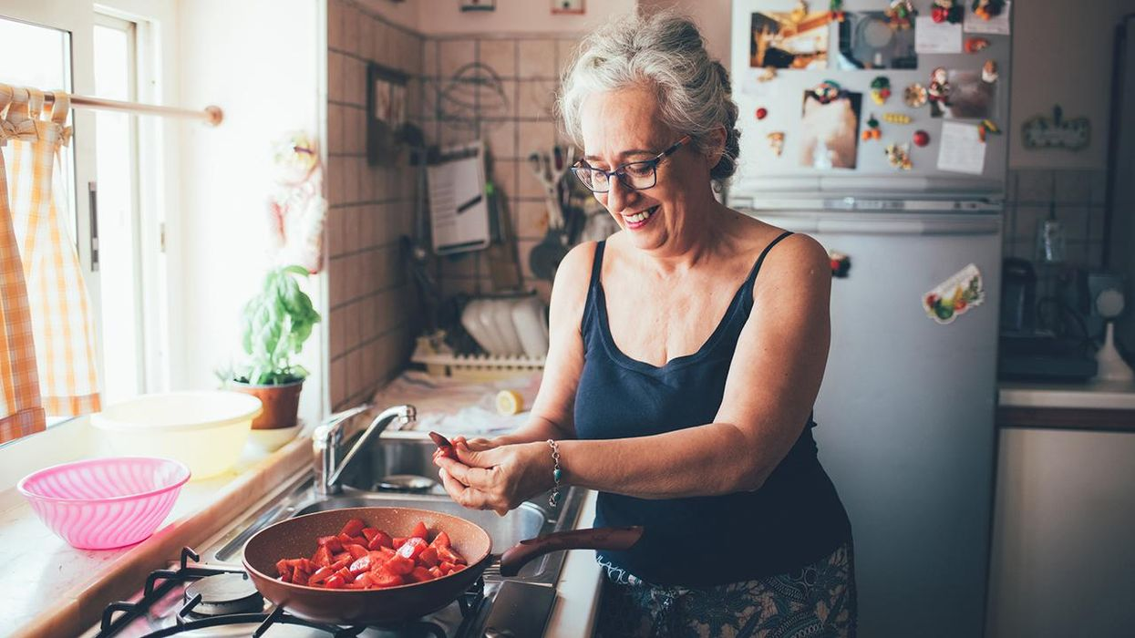 woman smiling making food in kitchen