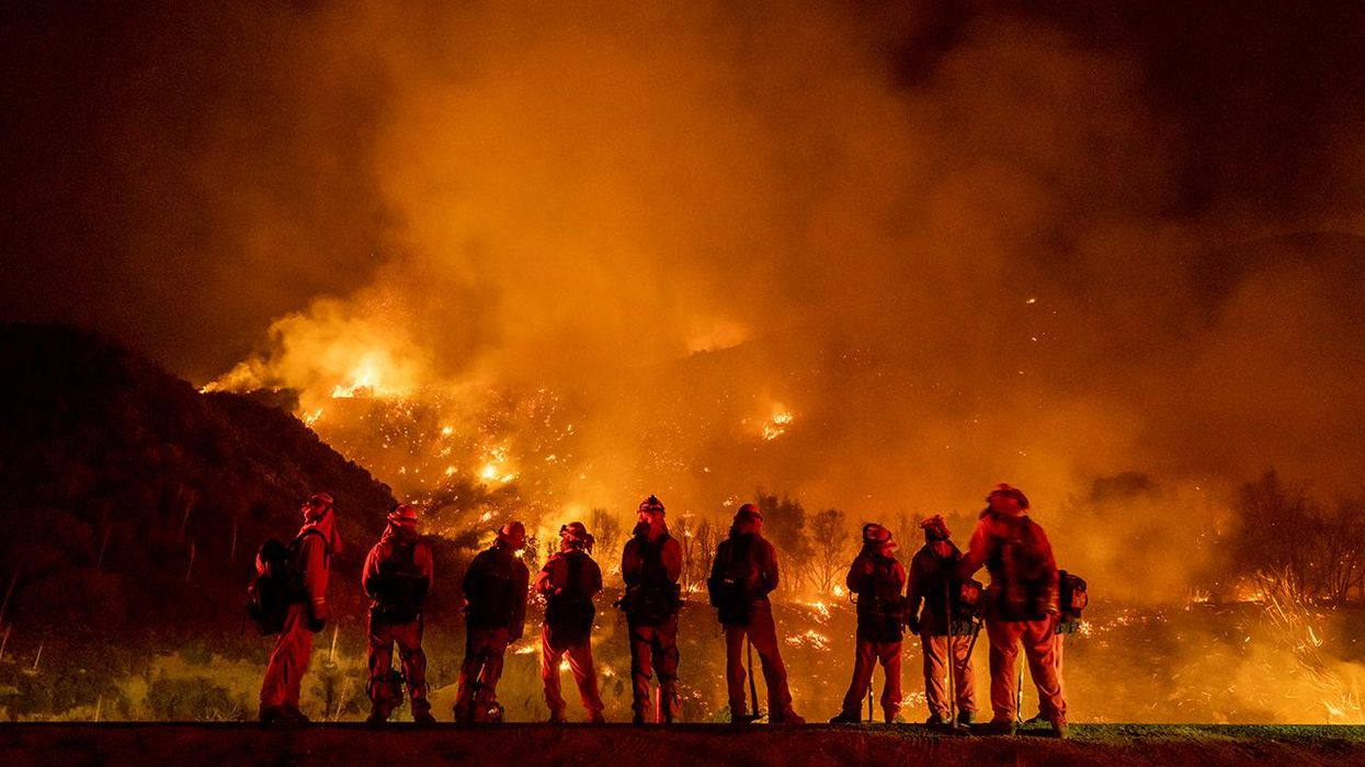 A group of inmate firefighter watch as wildfire burns
