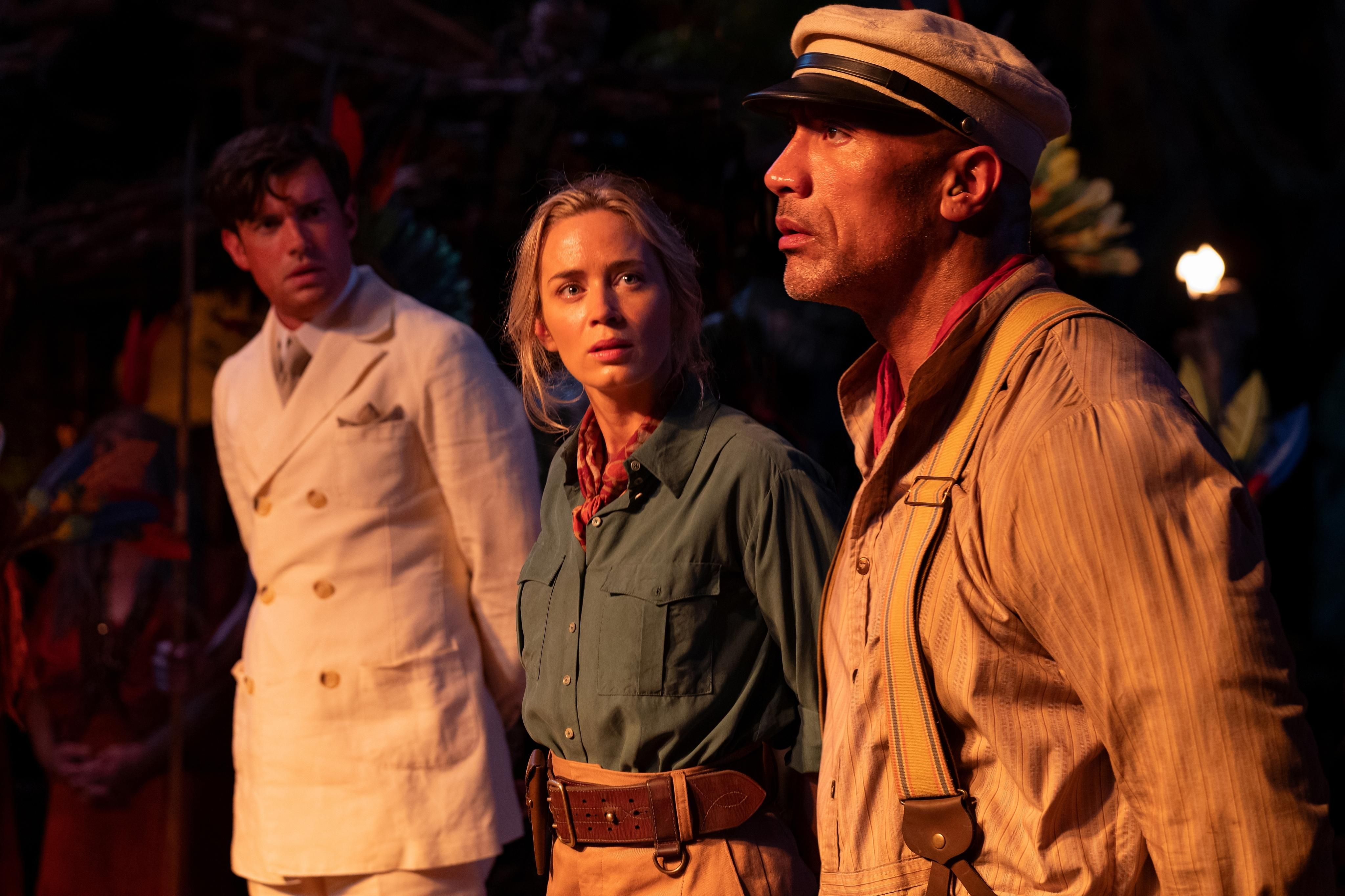 """From Left to Right: Macgregor (played by Jack Whitehall), Lily (played by Emily Blunt) and Frank (played by Dwayne Johnson) are standing side by side in a movie still from Disney's """"Jungle Cruise."""""""