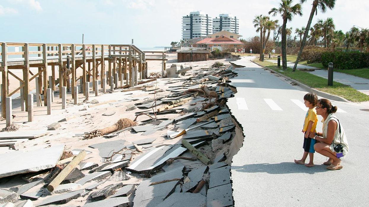 A mother and son looking at the missing road at beach damaged by hurricane