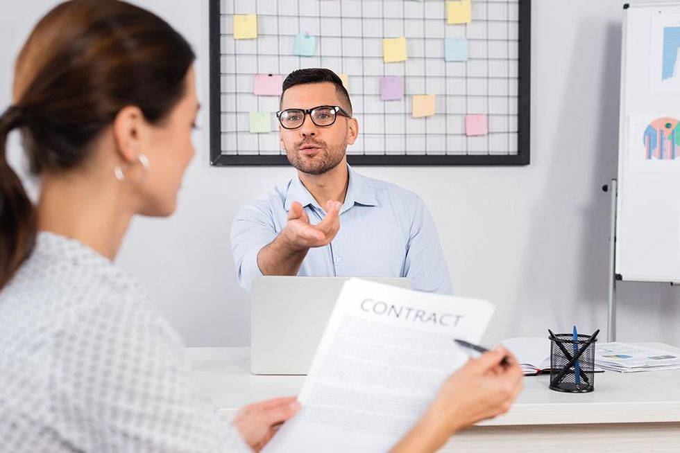 Woman checks her employment contract with her boss