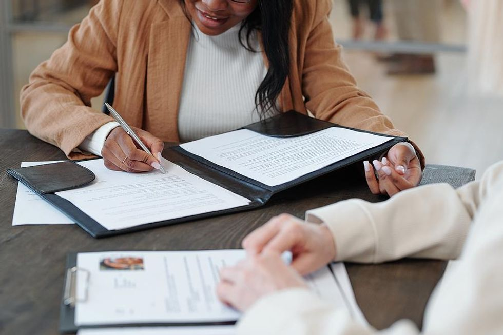 Woman signs an employment contract after a job interview
