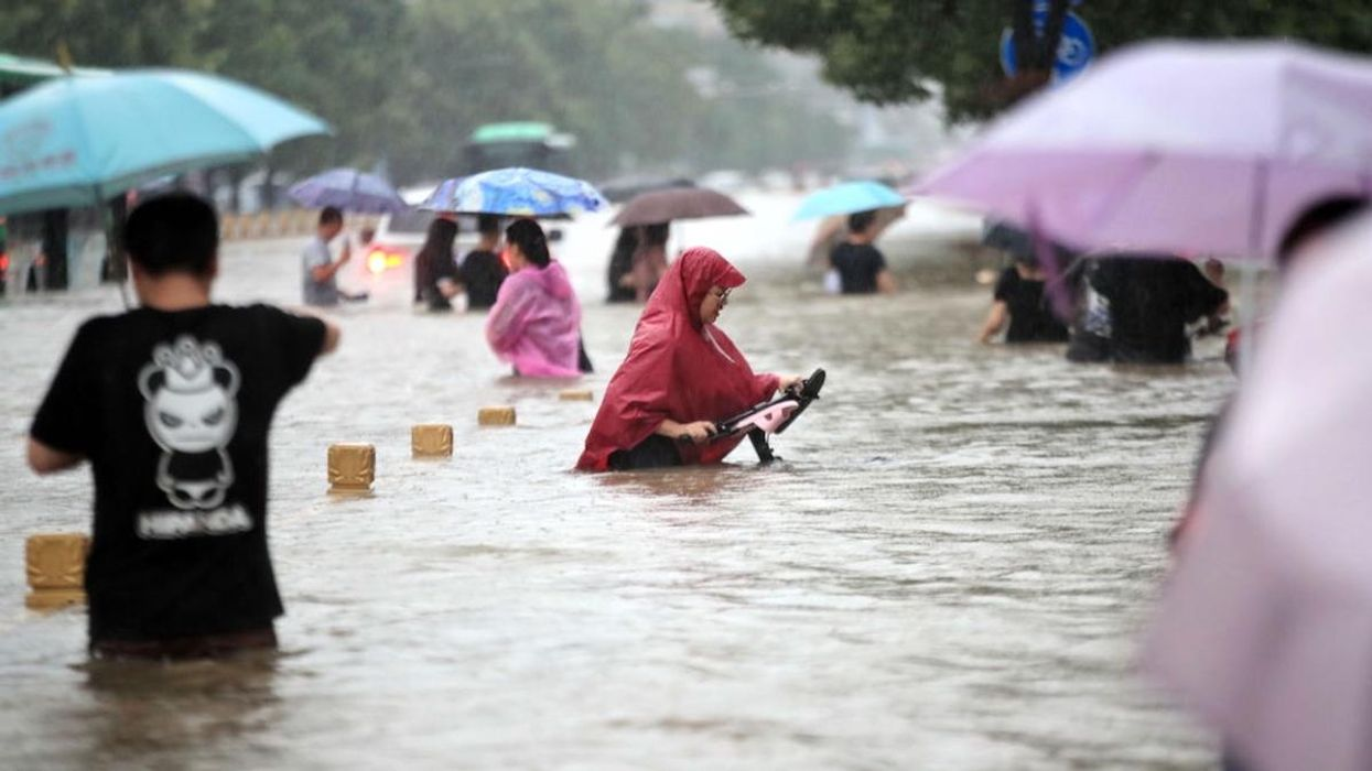 People walk in a flooded road in Zhengzhou city, China.