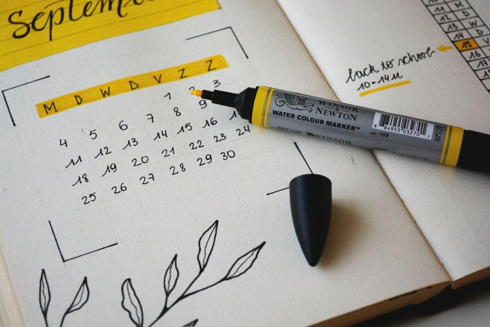 A black, white, and yellow calendar, with floral decals in the corner and yellow highlighter laying across the page.